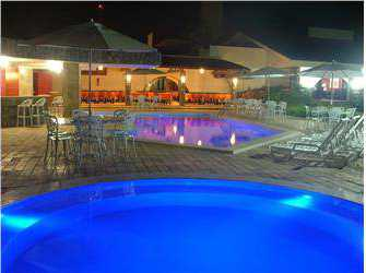 Imagem das piscinas e restaurante á noite.